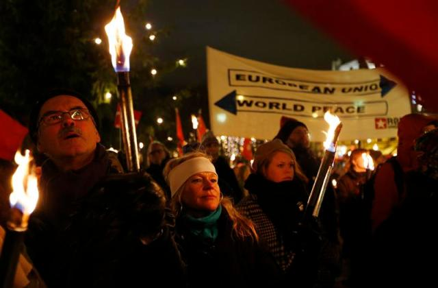 People hold torches during a protest rally outside of The Storting in Oslo